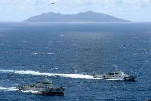 El barco de vigilancia chino Haijian No.51 (izquierda), navega cerca de la embarcación de la Guardia Costera de Japón (derecha), en las inmediaciones de las islas llamadas Diayou en China y Senkaku en Japón (al fondo).