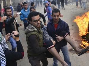 Dos personas ayudan a un herido durante los enfrentamientos. MOSTAFA DARWISH
