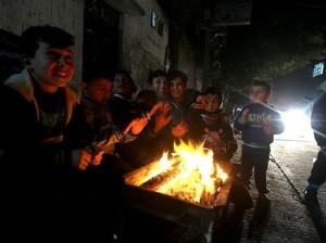 Niños palestinos en Gaza pasan la noche junto al fuego debido a los cortes de luz.